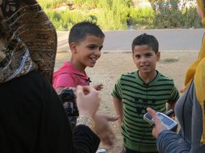 Two boys standing, smiling, during filming