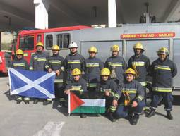 Firefighters with fire engine and flags of Scotland and Palestine